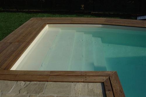 piscina interrata, particolare scala di accesso in opera con bordo in legno e pietra