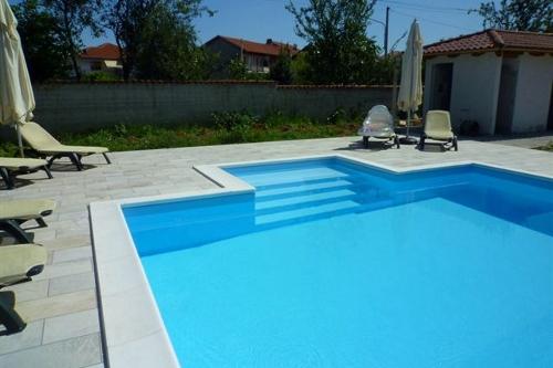piscina interrata, scala d'accesso dim. 2,50×2 m con ampia spiaggia in opera su lato corto