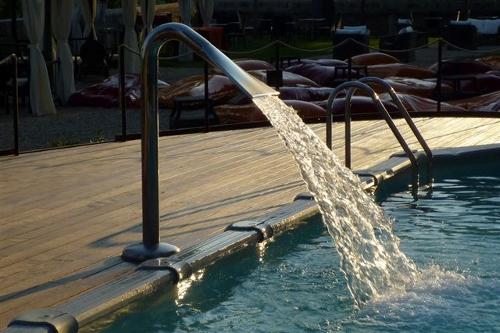 piscina fuori terra, particolare su fontana cascata ed area con Deck in legno