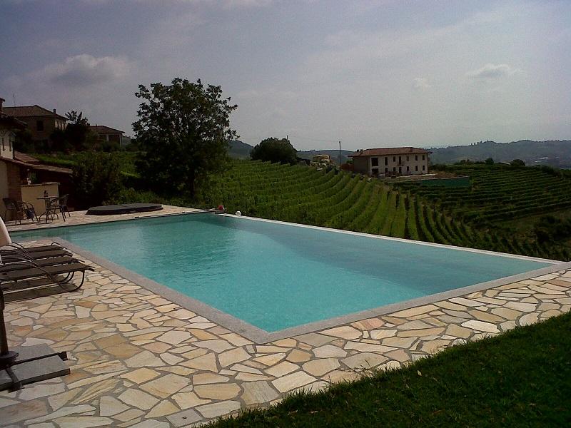piscina 12 x 6 m, con sfioro a cascata su lato lungo, scala ad appendice esterna, elettrolisi del sale e controllo automatico del pH