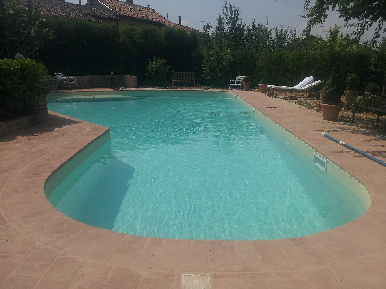 piscina 15 x 6 m a forma libera con spiaggia e scalinata in opera, nuoto contro corrente, circolazione a skimmer, rivestimento PVC armato color sabbia