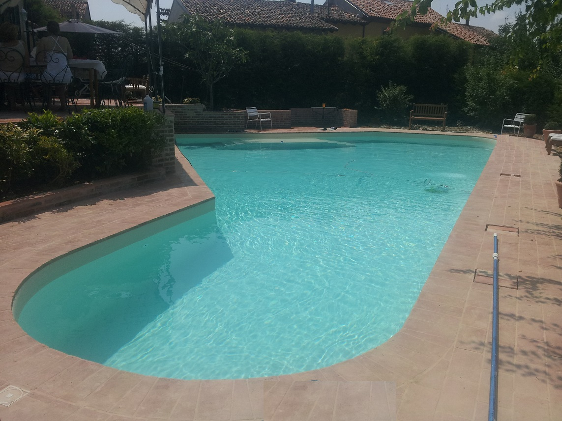 piscina 15 x 6 m a skimmer, forma libera, con spiaggia e scalinata in opera, nuoto contro corrente, elettrolisi del sale e controllo autom pH, rivest in PVC colore sabbia