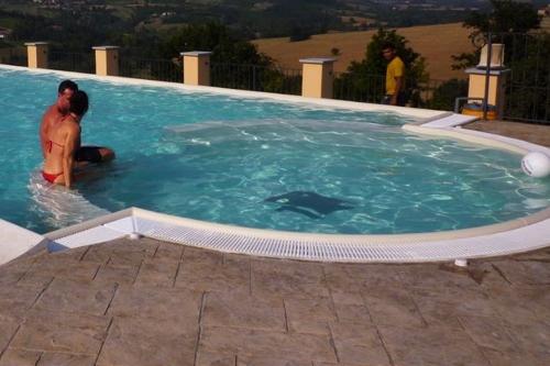 Area relax e giochi d'acqua in piscina interrata con sfioro e cascata a stramazzo