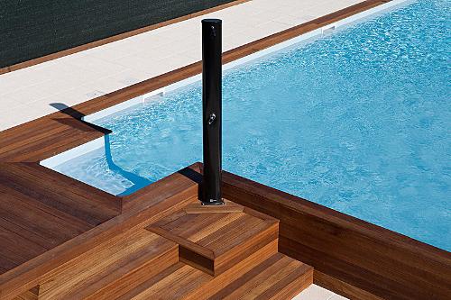 piscina interrata, particolare piscina a skimmer con scala laterale, doccia solare e pavimentazione in legno