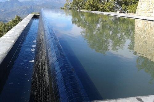 piscina a sfioro, particolare cascata con rivestimento in mosaico
