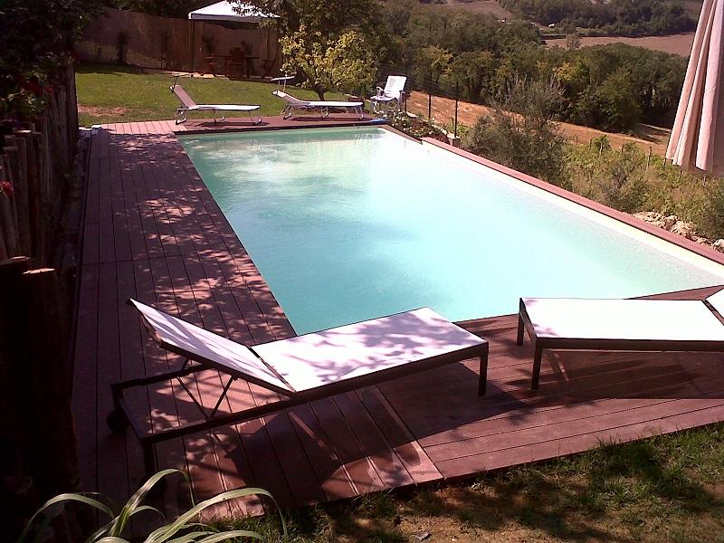 piscina 10x4 a cascata laterale, altezza composita, scala in opera interno vasca, acqua salata e controllo pH, rivestimento PVC armato color sabbia,esterno in deck color brown